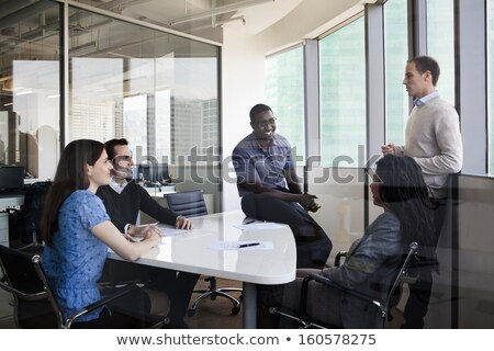 Side view of standing mixed race business people discussing over blueprint in the modern office. The Stock photo © wavebreak_media