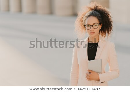 Photo of elegant African American businesswoman uses tablet computer outdoor, wears formal white jac Stock photo © vkstudio
