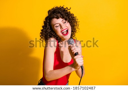 Stylish singer with curly red hair holding mic Stock photo © julenochek