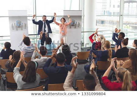 Rear view of diverse business people applauding and celebrating while they are sitting in front of m Stock photo © wavebreak_media
