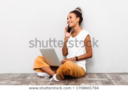 Young girl with dreadlocks using laptop computer. Stock photo © deandrobot