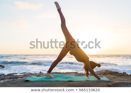 silhouette of a woman doing yoga on the beach at sunset stock photo © geribody