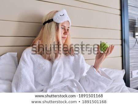 Young Woman in White Bathrobe Biting an Apple Stock photo © dash