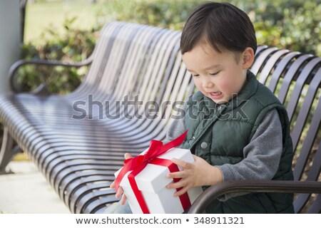 Сток-фото: Mixed Race Boy Opening A Christmas Gift Outdoors