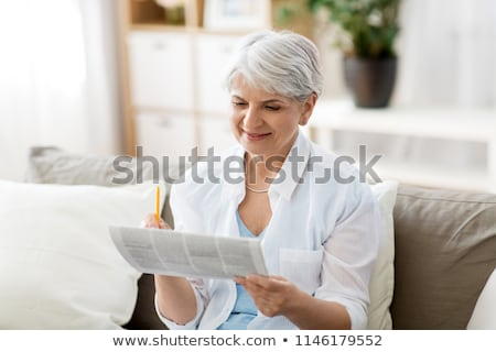 senior woman marking newspaper ad at home Stock photo © dolgachov