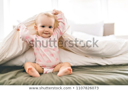 adorable baby girl cover with white sheet wearing pink clothes stock photo © lopolo
