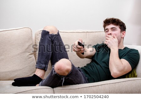 Man and young boy with remote control yawn Photo stock © Lopolo