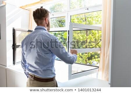 Vue arrière homme ouverture fenêtre air frais maison Photo stock © AndreyPopov