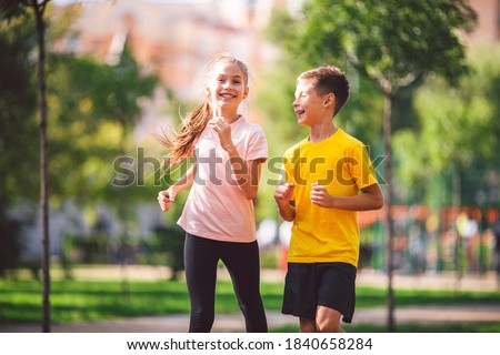 Two twins sportsmen brothers running at the stadium outdoors. Stock photo © deandrobot