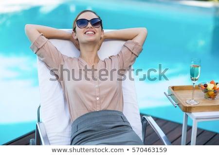 Yandan görünüş güzel genç kadın rahatlatıcı güneş cep telefonu Stok fotoğraf © wavebreak_media
