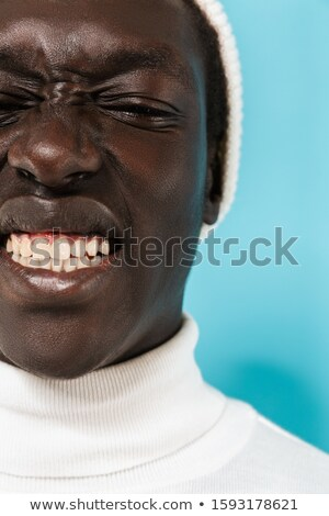 Image of joyous african american guy in white clothes smiling at Stock photo © deandrobot