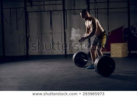 Attractive concentrated young fit sportsman getting ready to run Stock photo © deandrobot