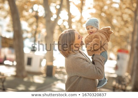 Mother and child on a walk in a public park hugs and kisses. Stock photo © ElenaBatkova