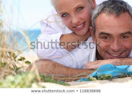Couple laid on towel at the beach Stock photo © photography33