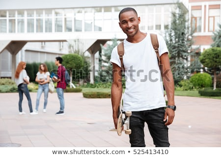Cheerful african man student with backpack holding skateboard outdoors Stock photo © deandrobot