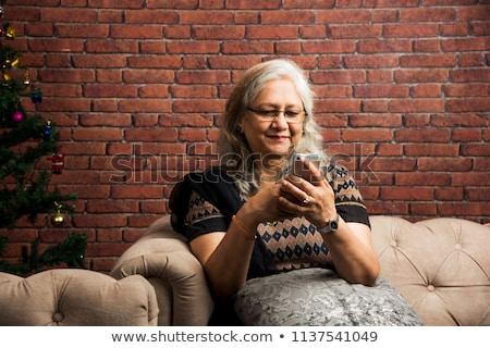 Dojrzały pani posiedzenia sofa starszy relaks Zdjęcia stock © Kurhan