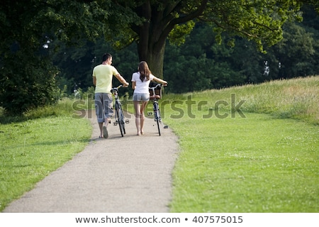 Woman cyclist pushing bicycle Stock photo © IS2