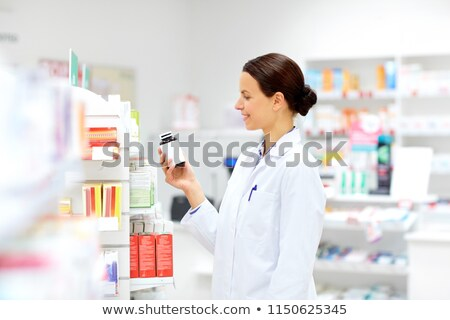 happy female apothecary with drug at pharmacy Stock photo © dolgachov