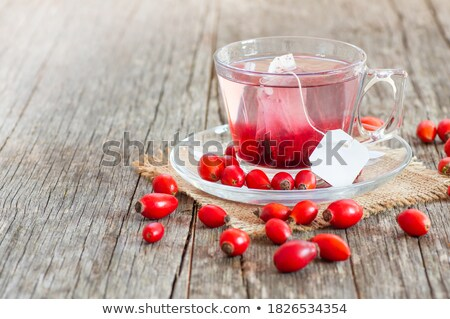 A cup of rose hip tea with fresh rose hips Stock photo © madeleine_steinbach
