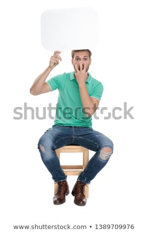 seated astonished man holds chat bubble up in the air Stock photo © feedough