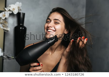 photo of smiling woman with long dark hair standing in bathroom stock photo © deandrobot