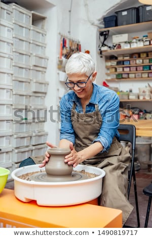Senior female potter working on pottery wheel while sitting  in  Stock photo © boggy