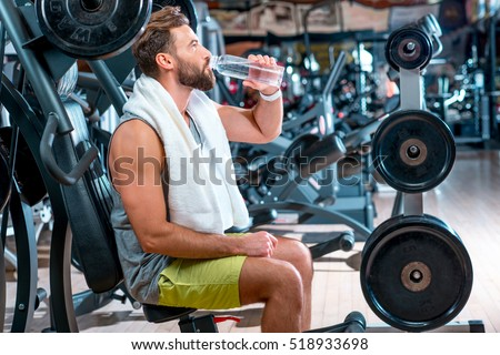 Stock photo: Sport man drinking water in the gym