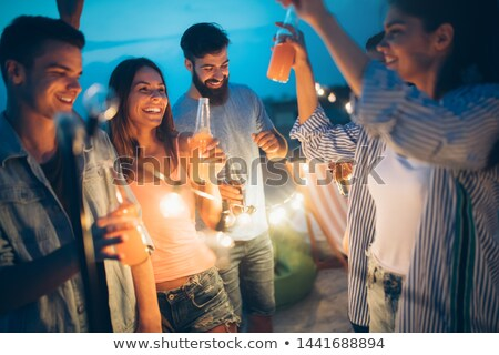 friends with drinks in party cups at rooftop Stock photo © dolgachov