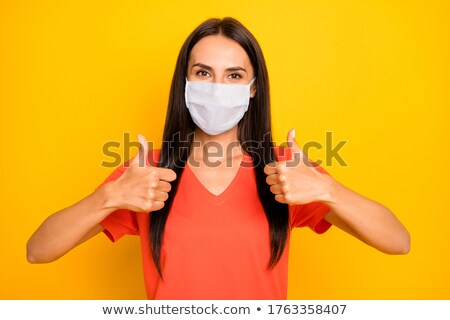 young woman showing double thumbs up stock photo © stockyimages