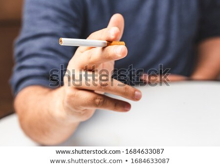 close up of hand holding cigarette between fingers Stock photo © dolgachov