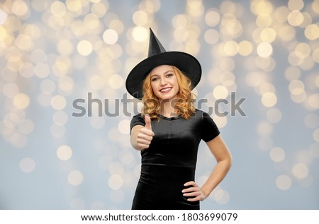 beautiful woman in black hat over holidays lights Stock photo © dolgachov