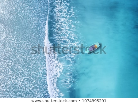 woman swimming with boat in background stock photo © is2