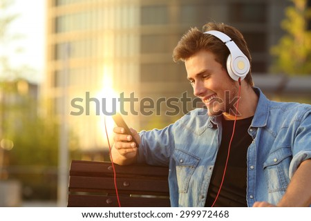Young guy sitting in park outdoors using mobile phone listening music with earphones. Stock photo © deandrobot