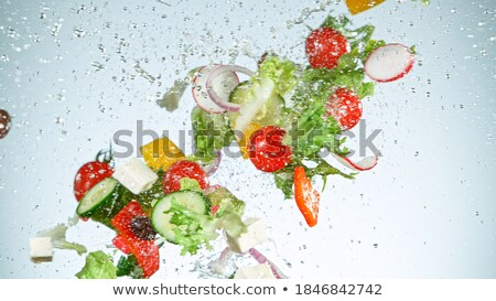 Grey bowl in motion with healthy fresh vegetables salad with lettuce and tomatoes, red onion and spi Stock photo © DenisMArt