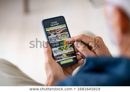 man orders food for lunch online using smartphone Stock photo © galitskaya