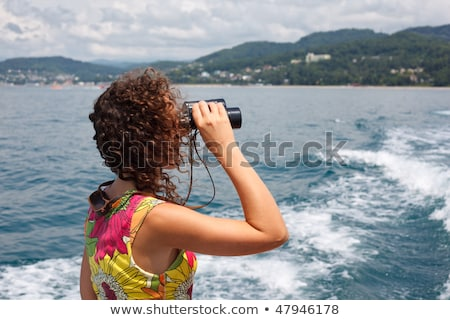 Sea tour, girl goes for drive on boat, observing in binocular sea coast. Stock photo © Paha_L