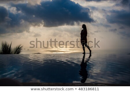 Woman sitting at swimming pool in Alp mountains Stock photo © Kzenon