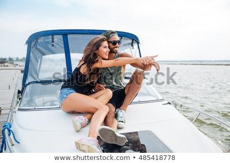 Para posiedzenia wskazując z dala jacht szczęśliwy Zdjęcia stock © deandrobot