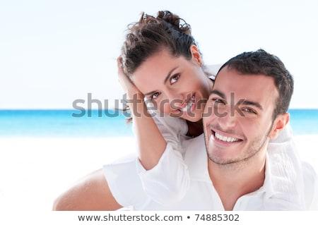 Man piggybacking smiling woman at beach Stock photo © wavebreak_media