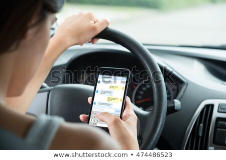 woman sitting inside car typing text message on cellphone stock photo © andreypopov