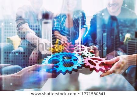 Working group of businessmen find the agreement by holding a piece of gear in hand. concept of teamw Stock photo © alphaspirit