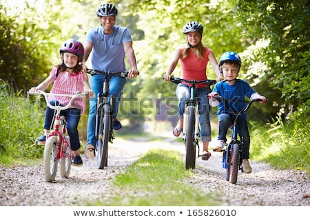 happy family is riding bikes outdoors and smiling father on a bike and son on a balancebike stock photo © galitskaya