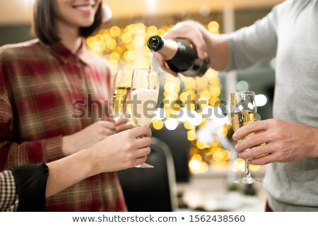 Hands of young businesspeople holding flutes while going to have champagne Stock photo © pressmaster