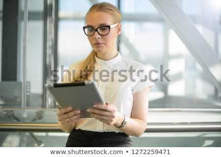 Serious office worker in formalwear watching video in smartphone or messaging Stock photo © pressmaster