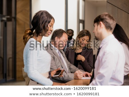 Group of contemporary businesspeople communicating by reception counter in hotel Stock photo © pressmaster