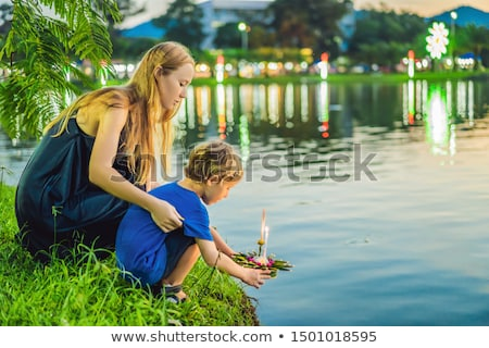 Mom and son tourists holds the Loy Krathong in her hands and is about to launch it into the water. L Stock photo © galitskaya