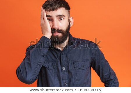 Image closeup of confused man with nose jewelry grabbing his fac Stock photo © deandrobot