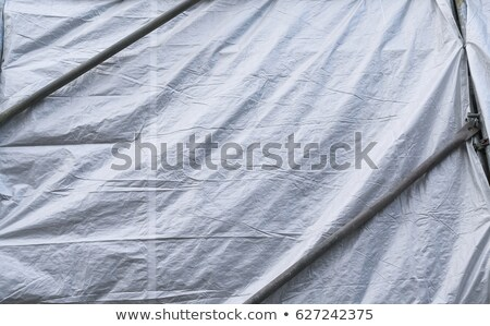 Building covered with wrinkled tarpaulin canvas Stock photo © Anterovium
