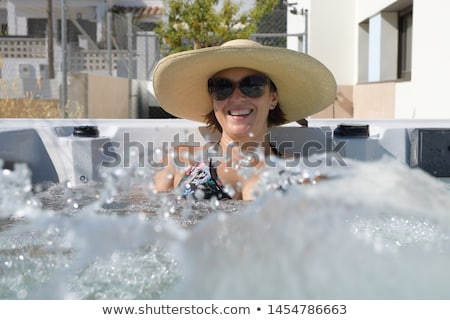Photo stock: Souriant · belle · femme · piscine · eau · éclaboussures · mains · tenant