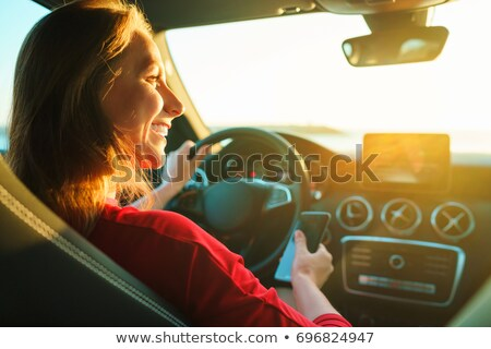 Happy woman uses a smartphone while driving a car Stock photo © vlad_star